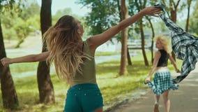 La mujer bonita del inconformista en pantalones cortos corre en parque Las chicas jóvenes se divierten y al aire libre metrajes