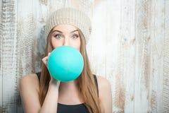La mujer bonita del inconformista está inflando el globo coloreado Imagen de archivo