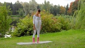 La mujer bonita delgada joven que hace aptitud ejercita para la salud del cuello en el parque cerca de un lago almacen de video