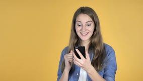 La mujer bonita emocionada para el rato del éxito usando Smartphone aisló en fondo amarillo almacen de metraje de vídeo