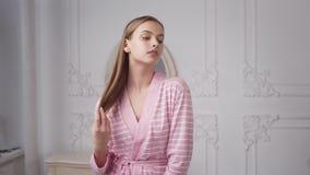 La mujer bonita en albornoz se está peinando el pelo largo en el dormitorio de la mañana litted con la luz del sol, cuidado del c metrajes