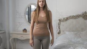 La mujer bonita en albornoz se est? peinando el pelo largo en el dormitorio de la ma?ana litted con la luz del sol, cuidado del c almacen de metraje de vídeo