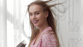 La mujer bonita en albornoz se seca el pelo por el secador de pelo en el dormitorio de la mañana litted con la luz del sol, cuida almacen de video