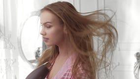 La mujer bonita en albornoz se seca el pelo por el secador de pelo en el dormitorio de la ma?ana litted con la luz del sol, cuida metrajes