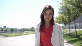 La mujer bonita en camisa roja camina afuera en un día soleado metrajes