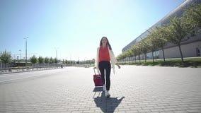 La mujer bonita en camisa roja camina con la maleta afuera en un día soleado metrajes