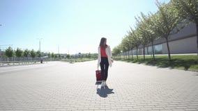 La mujer bonita en camisa roja camina con la maleta afuera en un día soleado almacen de metraje de vídeo