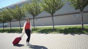 La mujer bonita en camisa roja camina con la maleta afuera en un día soleado almacen de video