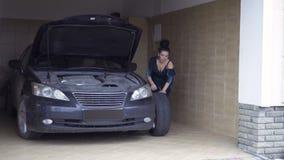 La mujer bonita en desarrollo del vestido el coche rueda adentro el garaje almacen de metraje de vídeo