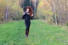 La mujer bonita en la chaqueta de cuero se coloca en hierba Foto de archivo libre de regalías