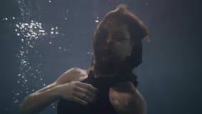 La mujer bonita en la natación negra del vestido le gusta la piscina subacuática de la sirena almacen de video