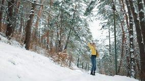 La mujer bonita en sombrero del invierno goza de la nieve y gira alrededor de exterior derecho en la nieve en el bosque almacen de metraje de vídeo