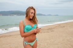 La mujer bonita escribe masaje en el teléfono móvil en la playa del mar Vietnam Foto de archivo libre de regalías