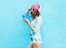 La mujer bonita escucha la música en auriculares usando smartphone sobre azul colorido Foto de archivo