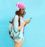 La mujer bonita escucha la música en auriculares usando smartphone sobre fondo azul Fotos de archivo