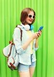 La mujer bonita escucha la música en auriculares usando smartphone sobre verde Imágenes de archivo libres de regalías