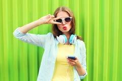 La mujer bonita escucha la música en auriculares y smartphone con sobre verde Imágenes de archivo libres de regalías
