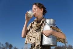 La mujer bonita está bebiendo la leche fresca Imagenes de archivo