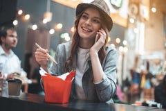 La mujer bonita está disfrutando de hablar en smartphone durante comidas Imágenes de archivo libres de regalías