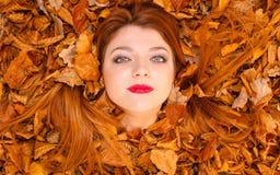 La mujer bonita está mintiendo entre las hojas Fotos de archivo