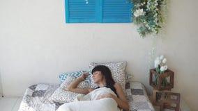 La mujer bonita está mintiendo pacífico en cama almacen de metraje de vídeo