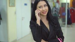 La mujer bonita está sosteniendo los panieres y está hablando un teléfono elegante en alameda metrajes