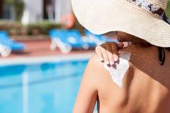 La mujer bonita est? aplicando la crema del sol en su hombro antes de broncear por la piscina Factor de protecci?n de Sun en las  imagenes de archivo