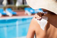 La mujer bonita est? aplicando la crema del sol en su hombro antes de broncear por la piscina Factor de protecci?n de Sun en las  imagen de archivo