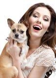 La mujer bonita guarda en las manos un pequeño perro Fotografía de archivo
