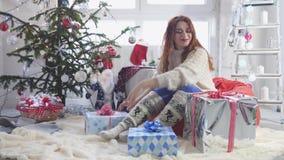 La mujer bonita joven abre una caja de regalo por un árbol de navidad Cámara lenta 3840x2160 almacen de metraje de vídeo