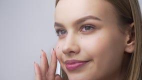 La mujer bonita joven aplica la crema de cara en sus pómulos, aplicando la crema en movimientos circulares, cuidado de piel, natu almacen de video