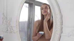 La mujer bonita joven aplica la crema de cara en sus pómulos y miradas al espejo, aplicando la crema en movimientos circulares almacen de video