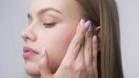 La mujer bonita joven aplica la crema de cara en sus p?mulos, aplicando la crema en movimientos circulares, cuidado de piel, natu metrajes