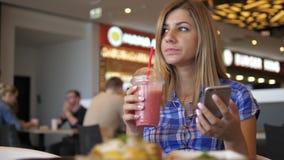 La mujer bonita joven bebe a Juice From el tubo al café, usando Smartphone metrajes