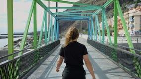 La mujer bonita joven camina en el puente del metal del arco iris almacen de video