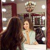La mujer bonita joven con compone y reflexión en vestuario Fotos de archivo