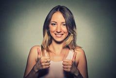 La mujer bonita joven con dos pulgares sube gesto de la muestra Fotografía de archivo libre de regalías