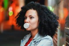La mujer bonita joven con el pelo afro muy rizado infla una bola de la burbuja del chicle blanco en la noche Muchacha de moda que fotos de archivo libres de regalías