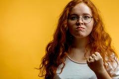 La mujer bonita joven del jengibre muestra el puño, con la expresión enojada o agresiva Imágenes de archivo libres de regalías