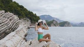 La mujer bonita joven en gafas de sol en traje de baño y con el sombrero ancho, se sienta en las rocas cerca del mar Vacaciones d metrajes