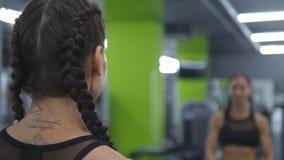 La mujer bonita joven entrena en el gimnasio que levanta y que baja pesas de gimnasia delante del espejo Muchacha de la aptitud d almacen de video