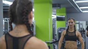 La mujer bonita joven entrena en el gimnasio que levanta y que baja pesas de gimnasia delante del espejo Muchacha de la aptitud d almacen de metraje de vídeo