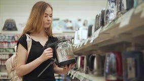 La mujer bonita joven está examinando la muestra de caldera eléctrica cerca del estante de la tienda metrajes