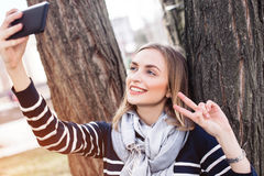 La mujer bonita joven está presentando mientras que se fotografía en el teléfono móvil para la imagen social de la red durante ti Imagenes de archivo