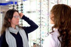 La mujer bonita joven est? intentando los vidrios del ojo encendido en una tienda de las gafas con ayuda de un ayudante y de las  imágenes de archivo libres de regalías