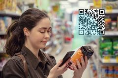 La mujer bonita joven explora un producto del código de QR en el supermercado El concepto de tecnolog?a moderna imagen de archivo libre de regalías