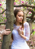 La mujer bonita joven goza en parque hermoso cerca de las flores Imagen de archivo