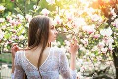 La mujer bonita joven goza en parque hermoso cerca de las flores Imágenes de archivo libres de regalías
