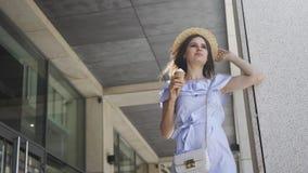 La mujer bonita joven lame el helado y la refrigeración en el centro de negocios metrajes