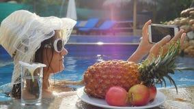 La mujer bonita joven lleva las gafas de sol y el sombrero toma el selfie con el teléfono móvil en piscina al lado de los vidrios Fotos de archivo libres de regalías
